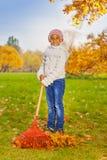 Ragazza africana che lavora con il rastrello rosso in parco da solo Immagine Stock
