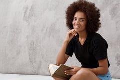 Ragazza africana che si siede e che sorride con il libro sopra fondo leggero Immagine Stock