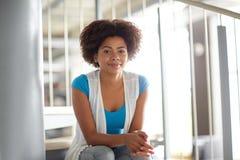 Ragazza africana felice dello studente che si siede sulle scale Fotografia Stock