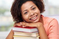 Ragazza africana felice dello studente con i libri a casa Fotografie Stock Libere da Diritti