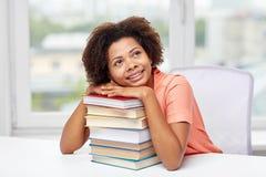 Ragazza africana felice dello studente con i libri a casa Immagini Stock