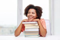 Ragazza africana felice dello studente con i libri a casa Immagini Stock Libere da Diritti