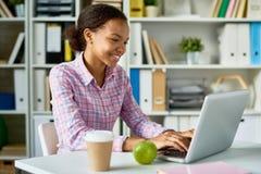 Ragazza africana sorridente che studia nella biblioteca immagine stock