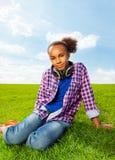 Ragazza africana su erba in cuffie d'uso di estate Immagini Stock