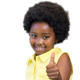 Ragazza africana sveglia con i capelli di afro che fanno i pollici su Immagine Stock