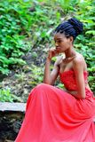 Ragazza africana in un vestito rosso, pensante e sedentesi nel parco su un fondo delle piante verdi Immagine Stock