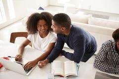 Ragazza afroamericana adolescente che fa compito con l'aiuto del suo papà, esaminantese, vista elevata immagine stock libera da diritti