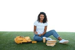 ragazza afroamericana adolescente dello studente che studia mentre sedendosi sull'erba Fotografia Stock