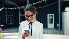 Ragazza afroamericana allegra che utilizza aria aperta dello smartphone nello schermo di contatto della via archivi video