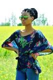 Ragazza afroamericana con i dreadlocks, gli occhiali da sole d'uso, jeans e una tunica, posante su un campo dei fiori gialli un g Fotografia Stock