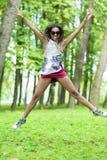 Ragazza afroamericana dell'adolescente con il salto steso delle mani Fotografie Stock