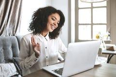 Ragazza afroamericana graziosa che si siede nel ristorante con il computer portatile Giovane ragazza sorridente che guarda in com Fotografia Stock