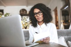 Ragazza afroamericana graziosa nel funzionamento di vetro sul computer portatile in ristorante Giovane signora con capelli ricci  Fotografia Stock