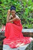 Ragazza afroamericana in un vestito rosso, con i dreadlocks, sedentesi di estate contro lo sfondo delle piante verdi sulle rocce Fotografia Stock