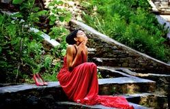 Ragazza afroamericana in un vestito rosso, con i dreadlocks sulla sua testa che si siede di estate sulle rocce nel parco Fotografia Stock