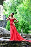 Ragazza afroamericana in vestito rosso e con le scarpe rosse in sua mano, stante con i suoi occhi chiusi di estate sulle rocce Immagini Stock Libere da Diritti