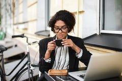 Ragazza afroamericana in vetri che si siedono alla tavola del caffè con il computer portatile e che tengono tazza di caffè in man Fotografie Stock Libere da Diritti