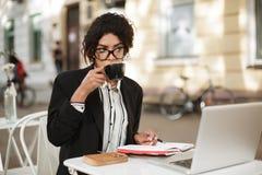 Ragazza afroamericana in vetri che si siedono alla tavola del caffè con il computer portatile ed il taccuino sulla tavola Signora Fotografia Stock Libera da Diritti
