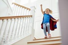 Ragazza agghindata come supereroe che gioca gioco sulle scale immagini stock libere da diritti
