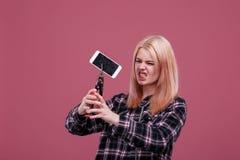 Ragazza aggressiva, smartphone delle rotture con il morsetto Su un fondo rosa immagini stock