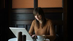 Ragazza al caffè con il computer portatile video d archivio