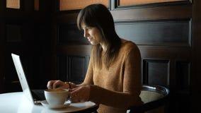 Ragazza al caffè con il computer portatile stock footage
