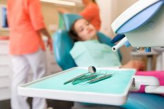 Ragazza al controllo del dentista ed al trattamento aspettanti, fuoco sulla borsa degli arnesi del dentista immagini stock