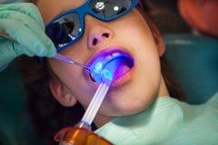 Ragazza al dentista che ottiene trattamento con luce blu dentaria immagine stock