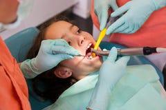 Ragazza al dentista, primo piano del controllo con gli strumenti del dentista fotografia stock