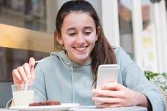 Ragazza al messaggio di testo della lettura del caffè sul telefono cellulare Fotografia Stock