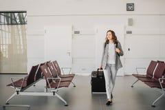 Ragazza all'aeroporto, camminante con il suo bagaglio immagini stock libere da diritti