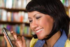 Ragazza alla libreria che legge un libro elettronico Fotografie Stock Libere da Diritti
