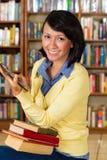 Ragazza alla libreria che legge un libro elettronico Immagini Stock