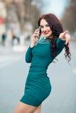 Ragazza alla moda alla moda con la buona figura esile in un vestito verde smeraldo verde dalla molla che parla sul telefono con i Immagine Stock Libera da Diritti