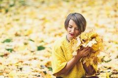 Ragazza alla moda in autunno, sedentesi sull'erba e tenente nel lotto delle mani delle foglie gialle fotografia stock libera da diritti