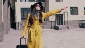 Ragazza alla moda in cappello giallo e vetri dell'impermeabile con attività ed i fermi dei bagagli un taxi video d archivio