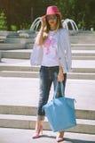Ragazza alla moda che posa davanti alla fontana fotografie stock