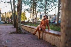Ragazza alla moda che si siede su un banco fotografie stock libere da diritti