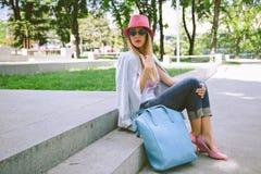 Ragazza alla moda che si siede sulle scale in parco fotografia stock libera da diritti