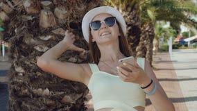 Ragazza alla moda che utilizza telefono cellulare sulla via nel giorno di estate caldo 4K stock footage
