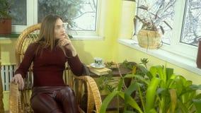 Ragazza alla moda con bello trucco che si siede di oscillazione di vimini guardare ed in una sedia fuori la finestra video d archivio