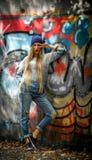 Ragazza alla moda con capelli biondi lunghi in vestiti alla moda che stanno su un fondo dei graffiti Fotografie Stock Libere da Diritti
