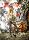 Ragazza alla moda con capelli biondi lunghi in vestiti alla moda che stanno su un fondo dei graffiti Immagine Stock Libera da Diritti