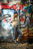 Ragazza alla moda con capelli biondi lunghi in vestiti alla moda che stanno su un fondo dei graffiti Fotografia Stock Libera da Diritti