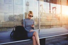Ragazza alla moda dei pantaloni a vita bassa che chiacchiera nella rete tramite Smart Phone con i suoi amici mentre sedendosi sul Immagini Stock Libere da Diritti