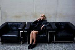 Ragazza alla moda dei pantaloni a vita bassa che telefona tramite telefono delle cellule mentre sedendosi su un sofà di cuoio ner Fotografie Stock Libere da Diritti