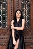 Ragazza alla moda e lussuosa in un vestito nero elegante sulla via, fem Fotografia Stock