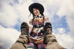 Ragazza alla moda felice del viaggiatore in gambe dell'uomo della tenuta del cappello e sorridere Immagini Stock