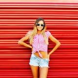 Ragazza alla moda in occhiali da sole che posano sopra la parete rossa immagini stock libere da diritti