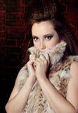 Ragazza alla moda in pellicce un muro di mattoni Fotografia Stock Libera da Diritti